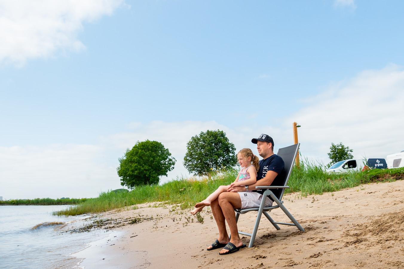 Stephan Zijdel en Faye Blinksma (5 jaar) die op de Stadscamping Schoonhoven verblijven denken er niet aan om in het water van de Lek te gaan. Zwemmen in de rivier is momenteel gevaarlijk door de zeer sterke stroming en het vele vuil dat wordt afgevoerd vanuit de Rijn.