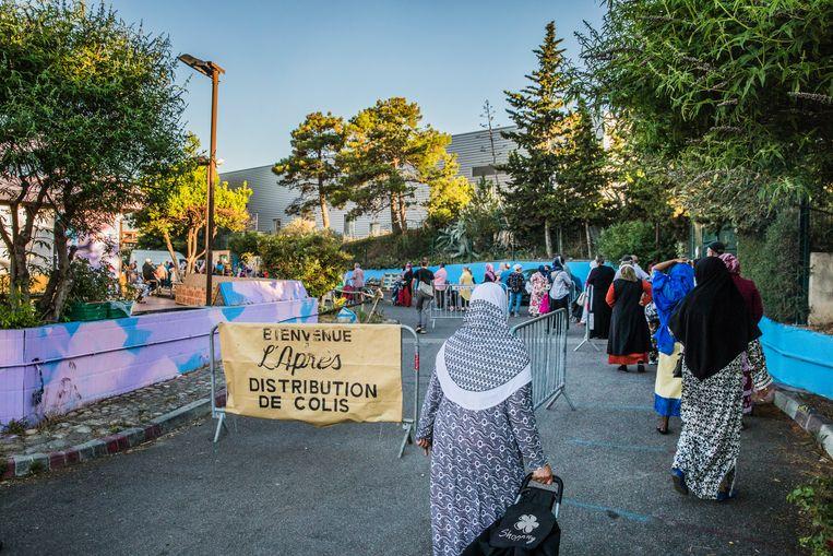 Lange rijen voor de voedselbank L'Après M. Alleen al in de eerste vijf weken ontvingen honderdduizend mensen hier een voedselpakket.   Beeld Aurélie Geurts