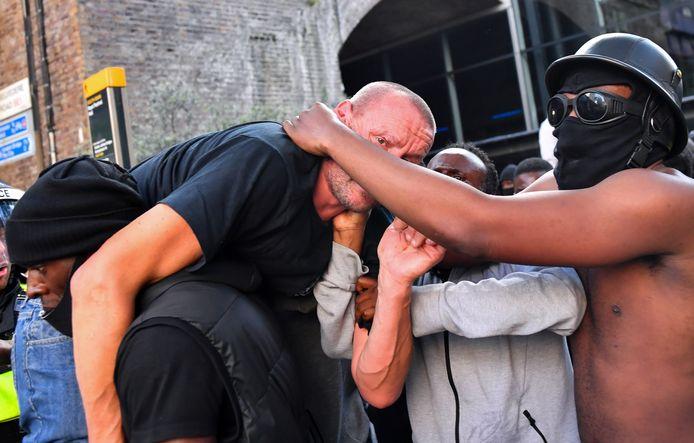 Een demonstrant brengt een gewonde tegen-demonstrant in veiligheid.
