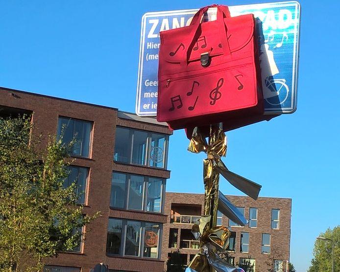 Een rode fietstas verhulde het zangfietspadbord tot de wethouders het fietspad openden.