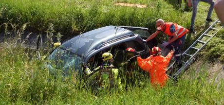 Auto belandt in sloot in Druten: twee personen en hond uit voertuig gehaald