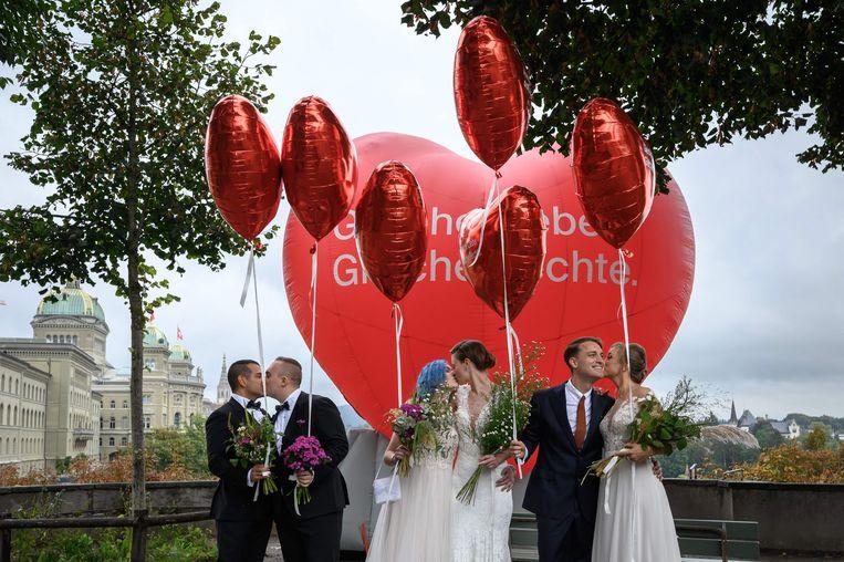 Op de dag dat de Zwitsers zich mochten uitspreken over de invoering van het homohuwelijk, poseerden deze verliefde voorstanders in Bern. Het ja-kamp behaalde in het referendum een overwinning, met een meerderheid van 64 procent.  Beeld FABRICE COFFRINI, AFP
