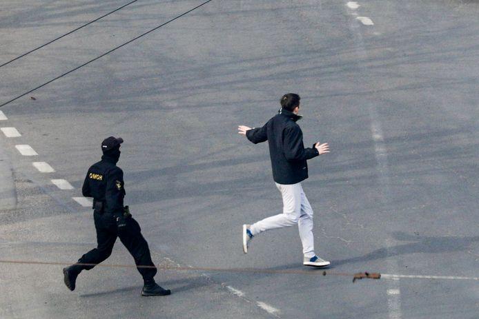 Een politieagent achtervolgt een demonstrant, gisteren in Minsk.