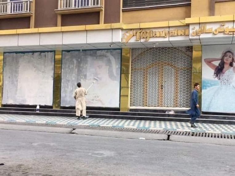 Een man beschildert de beeltenissen van vrouwen in het straatbeeld ter voorbereiding op de komst van de taliban. Beeld Twitter/Lotfullah Najafizada
