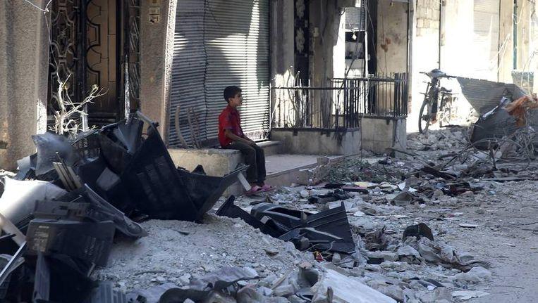 Een jongen zit in de verwoeste straten van Damascus Beeld reuters