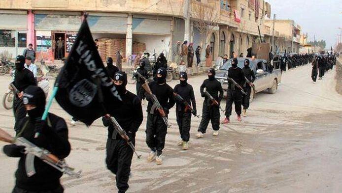 Militanten van Islamitische Staat marcheren door de straten van Raqqa.