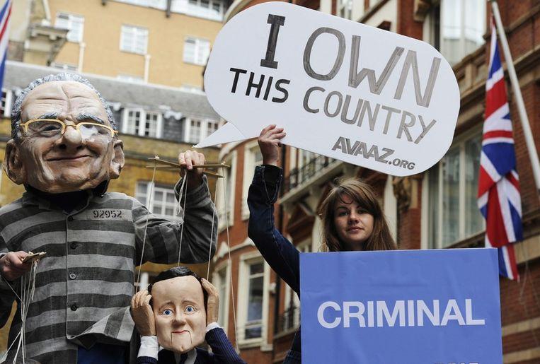 Een demonstrant heeft poppen gemaakt van Rupert Murdoch en zijn 'marionet' David Cameron. Beeld epa