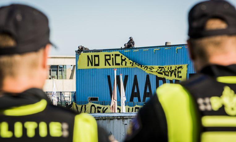De politie verwijdert spandoeken bij vrijplaats De Vloek in Scheveningen nadat de laatste krakers zijn opgepakt. Het terrein is geheel ontruimd. Beeld Freek van de Berg/de Volkskrant