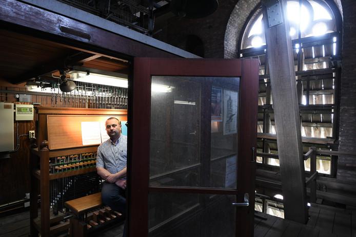 Stadsbeiaardier Wim Ruitenbeek bij het carillon in de toren van de Sint Maartenskerk.