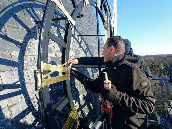 Ralf van Veghel op de hoogwerker bezig met een van de vier uurwerken op de toren van de Lamertuskerk in Gemonde.