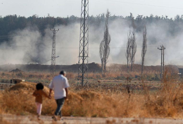 Mensen lopen in Akçakale in het zuidoosten van Turkije, terwijl op de achtergrond Turkse troepen vuren richting Syrië. Beeld AP