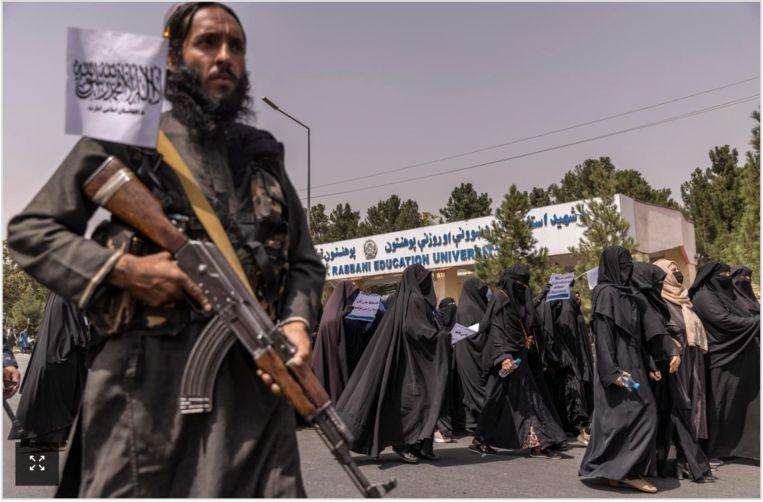 Vrouwen lopen niet toevallig op 11 september in een mars pro-taliban. Een strijder houdt een oogje in het zeil.  Beeld NYT