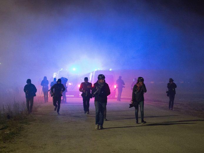 Journalisten rennen weg van de rellen omdat er traangas wordt ingezet.