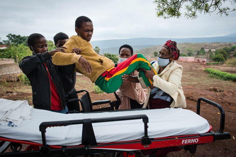 Machawe Lukhuleni wordt door zijn moeder Thembile Groening (rechts), broer, zus en de bestuurder van de ambulance (links) op een brancard getild om met een ambulance naar een fysiotherapie centrum te worden gebracht.  Beeld Bram Lammers