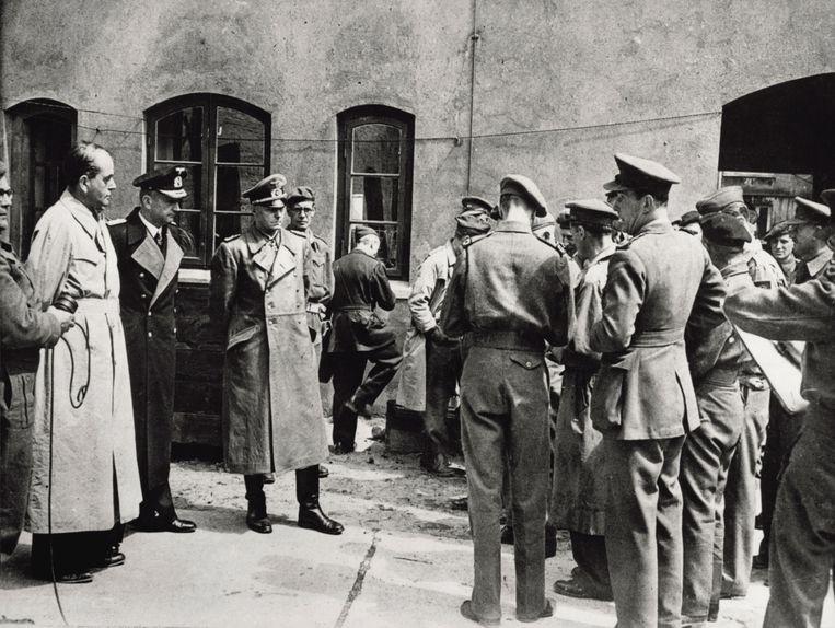 'Britse soldaten begeleiden Speer (links, in de bleke jas) samen met militaire nazi-kopstukken Karl Dönitz en Alfred Jodl naar de rechtszaal in Neurenberg.' Beeld Belga