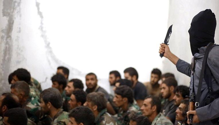Een IS-strijder bewaakt gevangen genomen soldaten van het Syrische leger bij een ingenomen luchtmachtsbasis bij Raqqa. Beeld ap