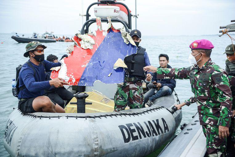Indonesisch marinepersoneel met een brokstuk van het zaterdag neergestorte vliegtuig. Beeld Via REUTERS