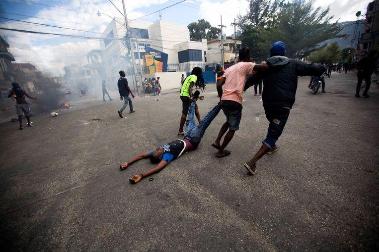 Demonstranten slepen het lichaam van een kameraad naar de politie die net in de menigte heeft geschoten, waarop de man dodelijk geraakt werd. Beeld AP