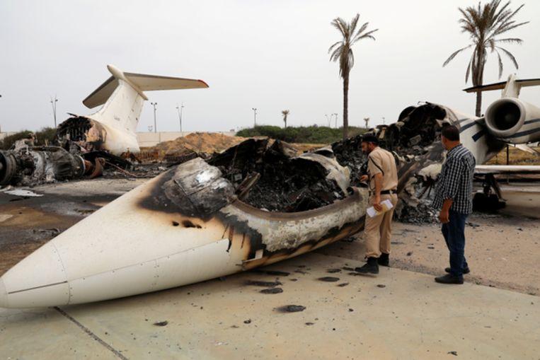 Een Libische agent en een man inspecteren een kapotgeschoten passagiersvliegtuig op de Mitiga-luchthaven in Tripoli, 10 mei 2020.   Beeld Ismail Zitouny / Reuters