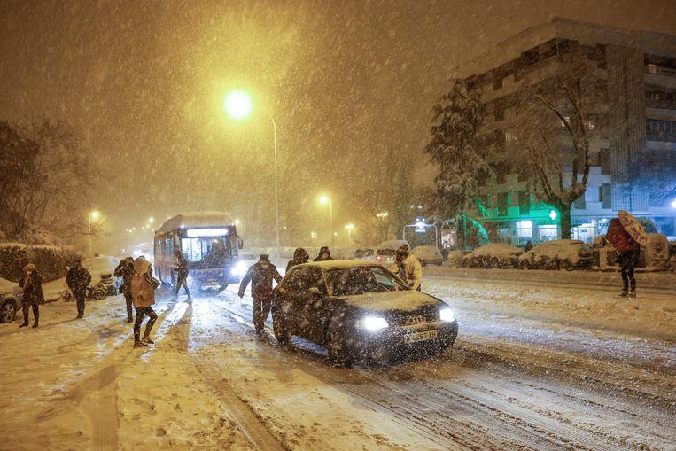 Mensen duwen een gestrande auto in de nacht van 8 op 9 januari. Beeld EPA