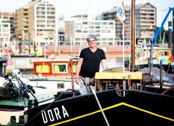 Oud en nieuw in Nijmegen-West: Eric Mol op zijn woonschip in de Waalhaven en op de achtergrond de nieuwbouw van de Handelskade.