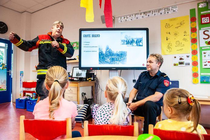 Leerlingen van basisschool De Ark in Bergambacht luisteren ademloos naar het verhaal van de brandweermannen Lejan Versluis en Evert Langerak over de allesverwoestende brand, die het dorp precies honderd jaar geleden trof.