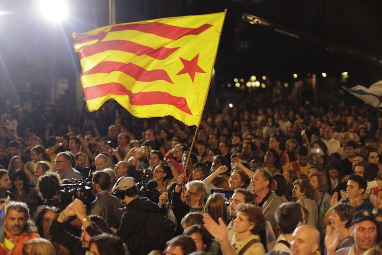 Voorstanders van de Catalaanse onafhankelijkheid zwaaien met de 'estelada' in Barcelona. Beeld AP