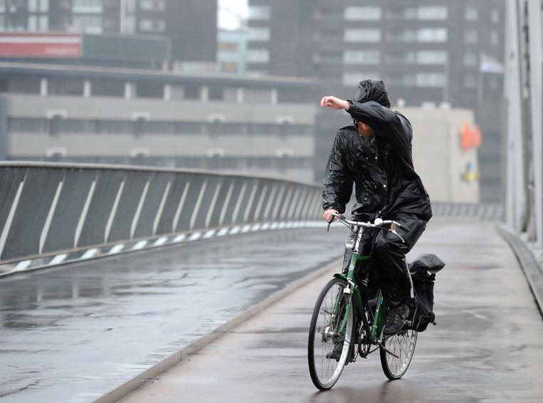 Een man trotseert de storm op de Erasmusbrug in Rotterdam. © ANP Beeld