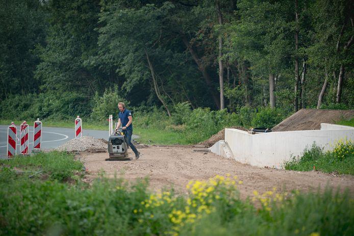 Een medewerker van Sallandse Wegenbouw bewerkt de ondergrond voor het nieuwe fietspad op de campus. Op de achtergrond het Dassenbos.