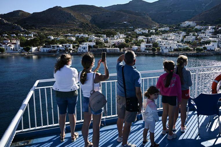 Reizigers maken foto's van het Griekse eiland Tilos vanop hun ferry. Beeld AFP