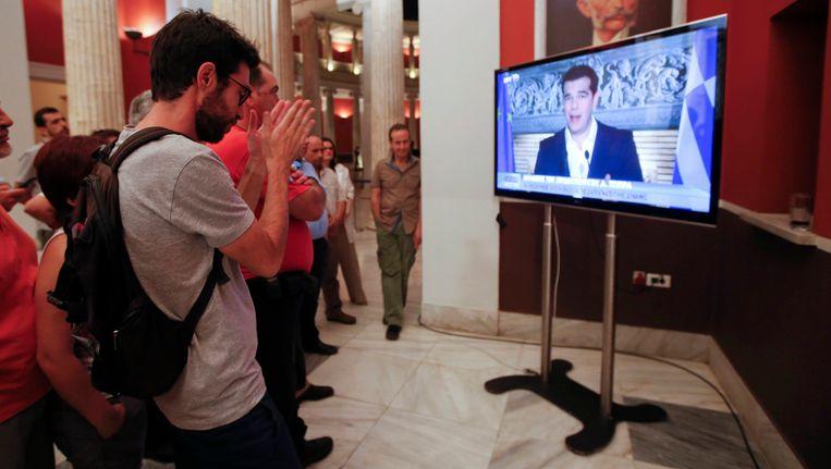 Grieken kijken naar de persconferentie van premier Tsipras. Beeld REUTERS