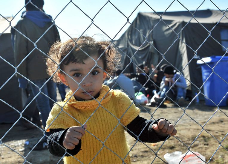 Een meisje houdt hekwerk vast in een vluchtelingenkamp in Slovenië. Beeld AFP