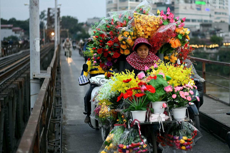 Een bloemenverkoper met haar koopwaar in Hanoi. Beeld AFP