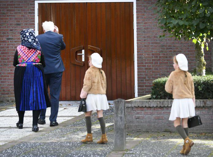 Kerkgangers komen aan bij de Hersteld Hervormde Kerk in het diepgelovige dorp Staphorst. In de grote kerk worden drie diensten met steeds zeshonderd mensen gehouden. Die hoeven geen mondkapje te dragen en er wordt wel gezongen.