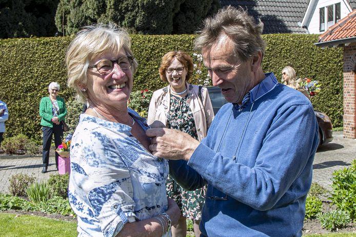 Anneke Roeloffzen-Demmer (69) uit Nijverdal krijgt haar lintje opgespeld door haar echtgenoot. Burgemeester Anneke Raven kijkt toe.