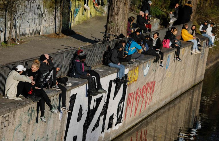Mensen genieten van de zon aan het kanaal in Kreuzberg, Berlijn. Merkel verstrengde de maatregelen 'omdat een minderheid van de Duitsers de ernst van de situatie niet inziet'. Beeld AFP