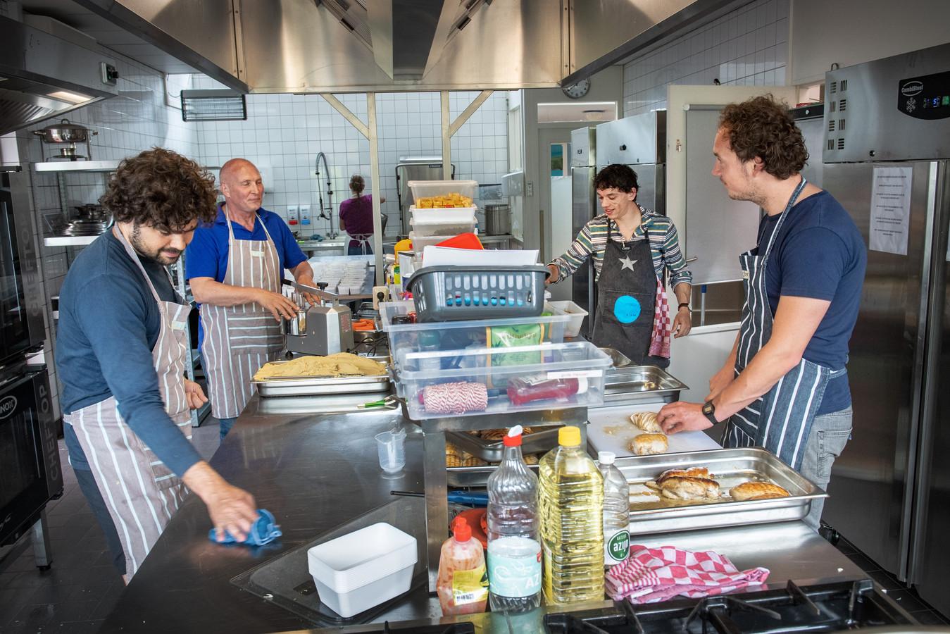 De koks van Berlin (links en rechts) en twee vrijwilligers van de Vincentius Vereniging bereiden de maaltijden voor. foto Bert Beelen