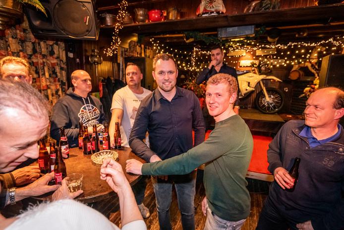 Deelnemers Wesley Pittens (midden) en Mark Tielemans (groene trui)  tijdens het uitzwaaifeest in café d'n Tieleman.