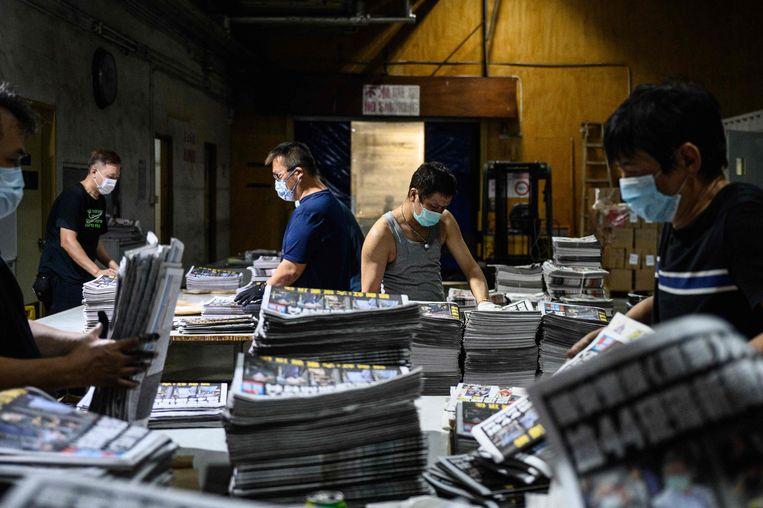 Medewerkers van de pro-democratische krant Apple Daily aan het werk op vrijdag 18 juni, de dag nadat de politie van Hong Kong binnenviel in hun kantoren en vijf leidinggevenden arresteerde. De politie zei dat er artikelen in de krant staan die in strijd zijn met de nieuwe nationale veiligheidswet van Hongkong. Beeld AFP