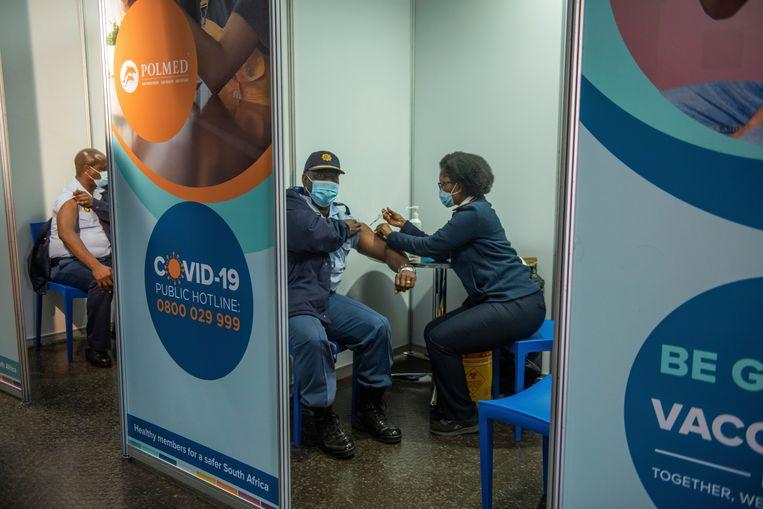 Zuid-Afrikaanse politieagenten krijgen een inenting tegen corona in Soweto.  Beeld AP