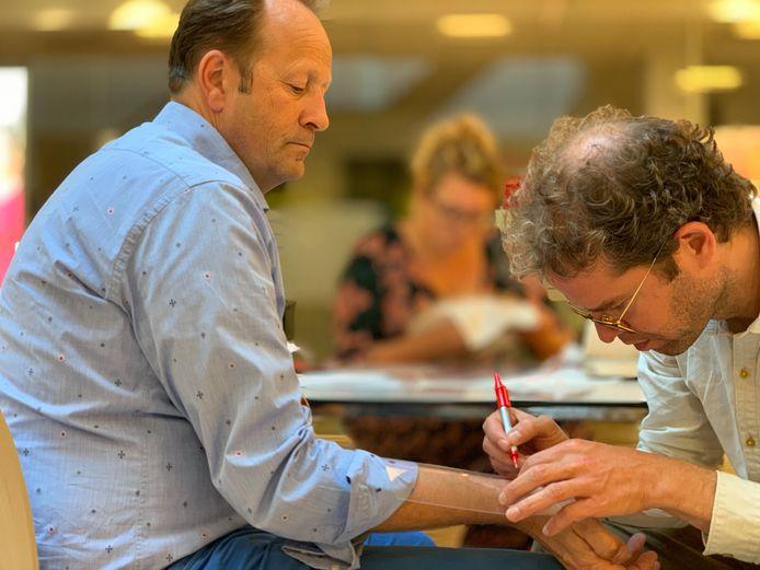 Joost van Wijmen maakt een overtrek van het litteken op de onderarm van Aart van Stiphout.