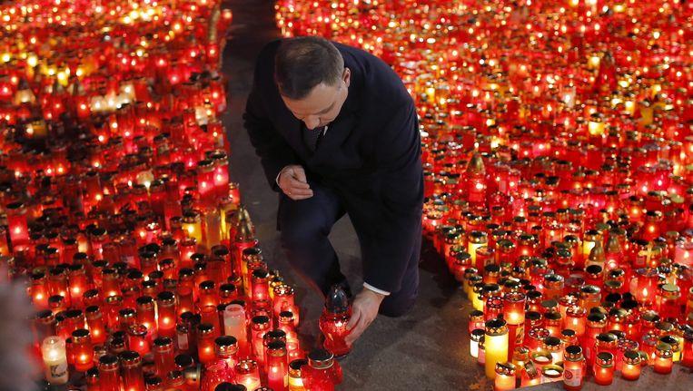 De Poolse president Andrzjez Duda plaatst een kaarsje nabij de nachtclub waar vorige week een brand uitbrak die 39 mensen het leven kostte. Beeld epa