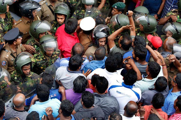 Agenten en betogers bij het kantoor van de Ceylon Petroleum Corporation in Colombo, waar de ontslagen minister van Olie naar zijn werk probeerde te gaan.  Beeld EPA