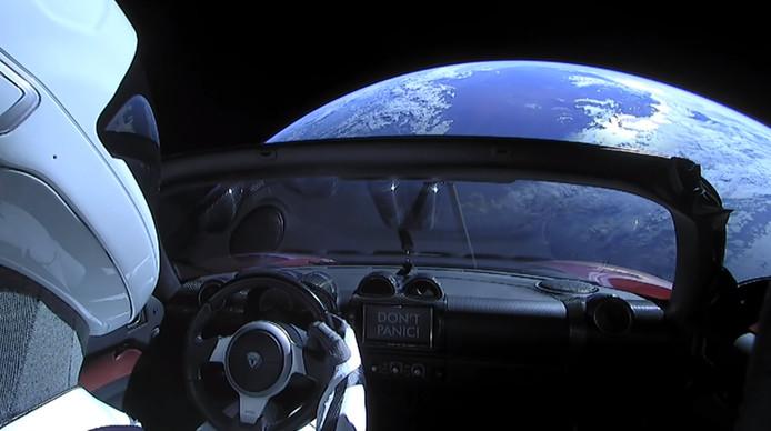 Het uitzicht van de rode Tesla Roadster in de ruimte.