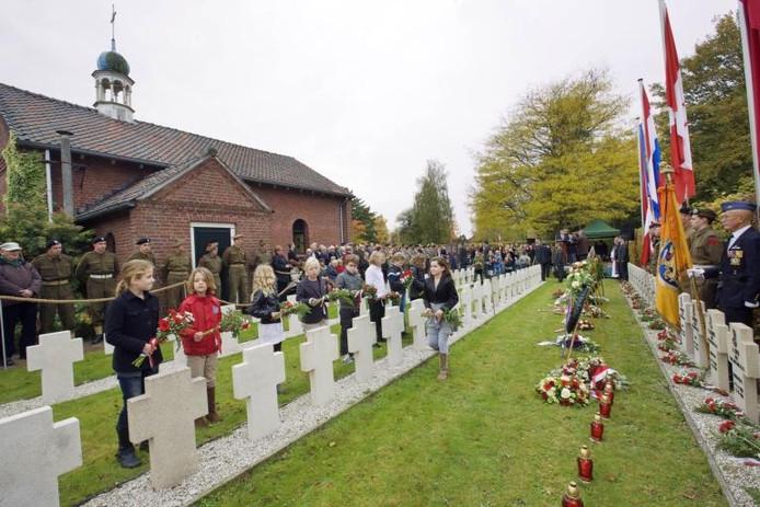 Kinderen leggen een bosje bloemen op de graven van de gesneuvelde Poolse soldaten op de begraafplaats aan de Vogelenzanglaan in het Ginneken.foto Charlotte Akkermans/het fotoburo