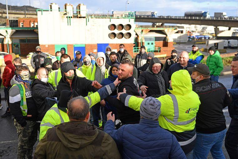 Havenmedewerkers proberen de boze chauffeurs in bedwang te houden. Beeld AFP