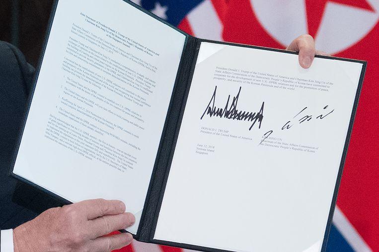 Trump toont het ondertekende document. Beeld AFP