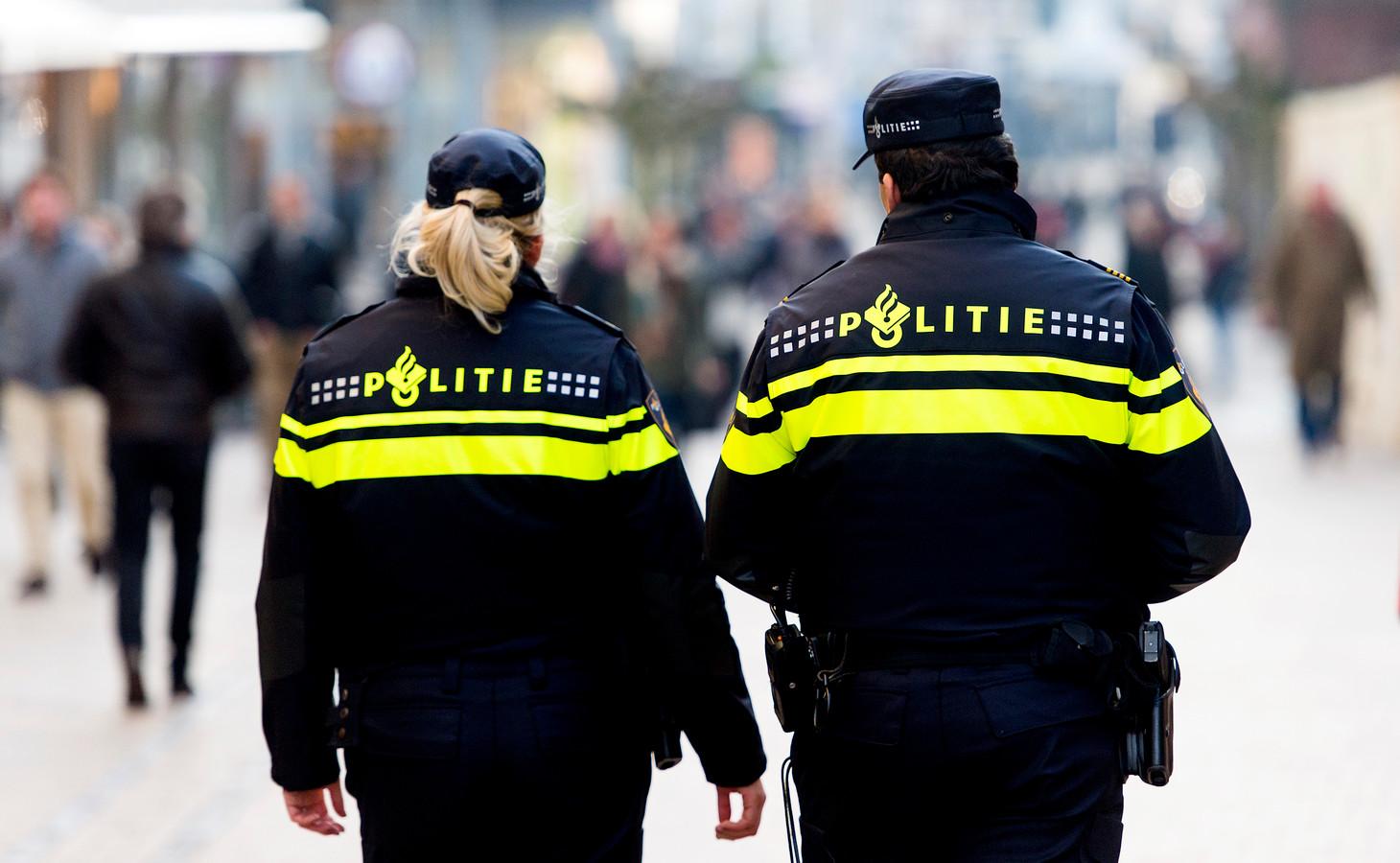 Politieagenten surveilleren in een winkelstraat.