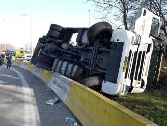 Nederlandse vrachtwagenchauffeur kantelt op afrit en komt naast weg terecht