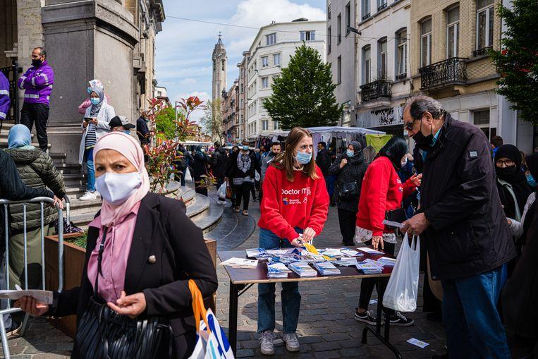 Op de markt van Sint-Jans-Molenbeek worden mensen aangesproken om zicht te laten vaccineren.  Beeld Wouter Van Vooren